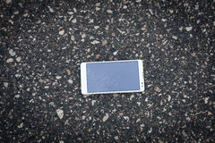 White phone with broken screen. Phone with broken screen lying on the street stock image