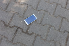 White phone with broken screen. Phone with broken screen lying on the street royalty free stock photo