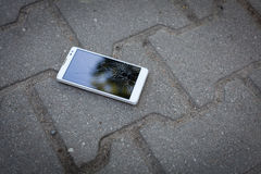 White phone with broken screen. Phone with broken screen lying on the street stock photo