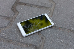 White phone with broken screen. Phone with broken screen lying on the street royalty free stock images