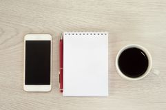 White phone with a cup of coffee, notepad and pen lie on a white wooden table stock photos