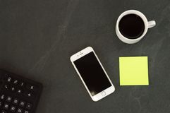 White phone with a cup of coffee, a red pen and a calculator lie on a white wooden table stock photo