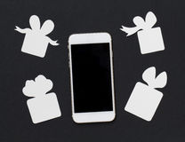 White phone with gift boxes on black background. Black and white banner template with smartphone and paper cut presents. Stock Photos