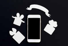 White phone with gift boxes and blank ribbon banner on black background. Stock Images