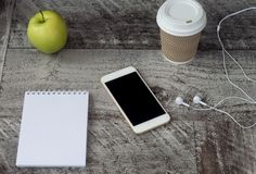 White phone with headphones, coffee, notepad and green apple on the table. Work at home. Freelance royalty free stock photo