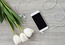 A white phone with white headphones and white tulips lies on a white wooden table stock photography