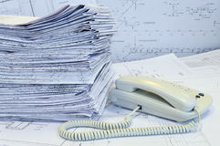 White phone and heap of formed project drawings. White phone and heap of formed engineering drawing are on the surface covered by working drawings (papers) Stock Image