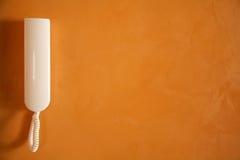 White phone on orange wall. White phone on modern orange wall Stock Photo