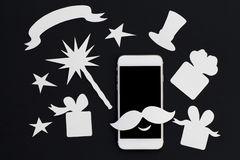 White phone in paper cut collage with magic wand and presents. Royalty Free Stock Photo