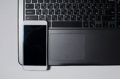 A white phone rests on a laptop keyboard. A white phone rests on a black laptop keyboard, on a white background Stock Photos