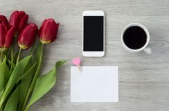 White phone with a sheet of paper lies on a white wooden table with a cup of coffee and red flowers.  stock photos