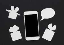 White phone with text bubble and gift box on black background. Stock Images