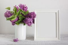 White photo frame and bouquet of purple lilac flowers in vase. Space for text. Vintage. Mother day mock up stock photo