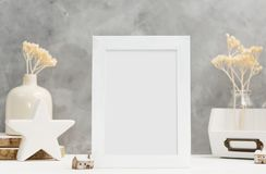 White Photo frame close up mock up with plants in vase with wooden and ceramic home decor on shelf. Scandinavian style. Text space royalty free stock images