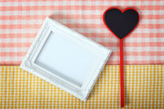 White photo frame with heart sign from wooden over fabric, clipp Royalty Free Stock Images