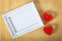 White photo frame next heart sign from candle over yellow fabric Stock Image