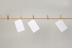 White photo paper. Hanging on a clothesline with clothespins. Royalty Free Stock Photography
