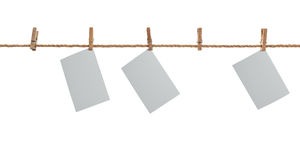 White photo paper. Hanging on a clothesline with clothespins. Royalty Free Stock Photo
