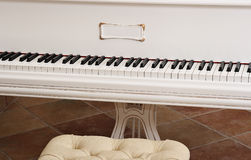 White piano. The keyboard of a white piano and a chair standing in front of it royalty free stock photos