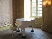 White piano in classy environment. White piano wheeled and stool parked in the corner of a wedding hall royalty free stock image