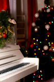 White piano in the New Year's room. Boke on the Christmas tree Royalty Free Stock Photos