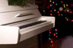 White piano in the New Year's room. Boke on the Christmas tree Stock Photos
