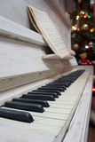 White piano. Old white piano with notes on it and Christmas tree in the background Royalty Free Stock Photo