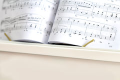 White piano with piano notes. Close up royalty free stock photography