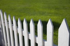 White Picket Fence. With green grass background Stock Photos