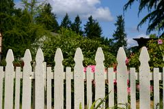 White picket fence. Picket fence against residential garden, blue sky royalty free stock photos