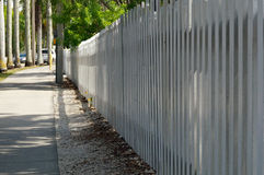 White picket fence along sidewalk Royalty Free Stock Images