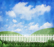White picket fence. A white picket fence with a blue cloudy sky and green hills Royalty Free Stock Photo