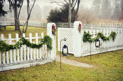 White Picket Fence. A white picket fence decorated for Christmas with evergreen swags on a foggy, misty, morning.  There are also two oil lanterns hanging out Royalty Free Stock Photo