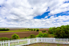 White Picket Fence, Farmland, and Clouds Royalty Free Stock Image