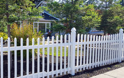 White picket fence. In the foreground with trees and house in the background royalty free stock photography