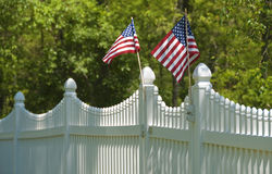 White picket fence, july 4th. White picket fence with green grass background topped by two American flags, ready for the 4th of july Royalty Free Stock Photography