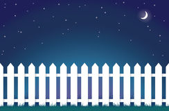 White picket fence at night Stock Photos