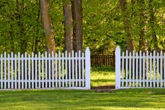 White Picket Fence in Park. A white picket fence with an open gate to the park Stock Image
