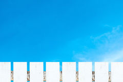 White picket fence and soft white clouds blue sky. White picket fence and soft white clouds against blue sky Stock Photos
