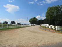White picket fence stretching down road Stock Images