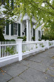 White picket fence by a typical federal style house Royalty Free Stock Photography