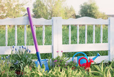 White picket garden fence with watering can and shovel Stock Photos