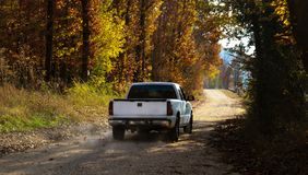 White pickup truck driving down dusty dirt road with fall leaves and dust behind. A White pickup truck driving down dusty dirt road with fall leaves and dust Royalty Free Stock Photo