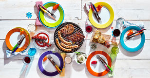 White picnic table set with colorful dinnerware Royalty Free Stock Photos