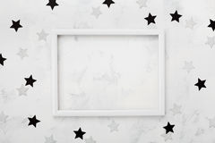 White picture frame with black and silver stars around for fashion blogging mockup. Top view and flat lay. Royalty Free Stock Photography