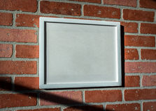 White Picture Frame on Red Brick Wall Landscape Angled. Add your own text to this image or download the PNG with transparent frame area to insert your own stock image