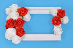 White picture frame surrounded by red and white foam rose flower blossoms on blue background