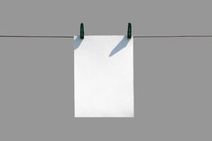 The white piece of paper hanging on rope with clothespins. Close Royalty Free Stock Photography