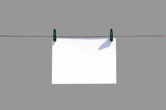 The white piece of paper hanging on rope with clothespins. Close Stock Photo