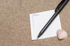 White piece of paper with written plan on sea sand, business concept Royalty Free Stock Photos